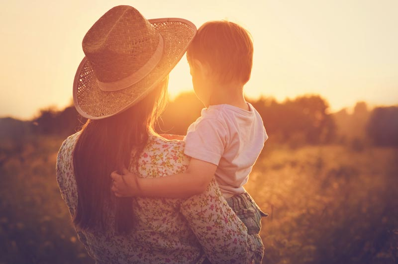 A woman wearing a straw cowboy hat while holding her child and watching the sun rise