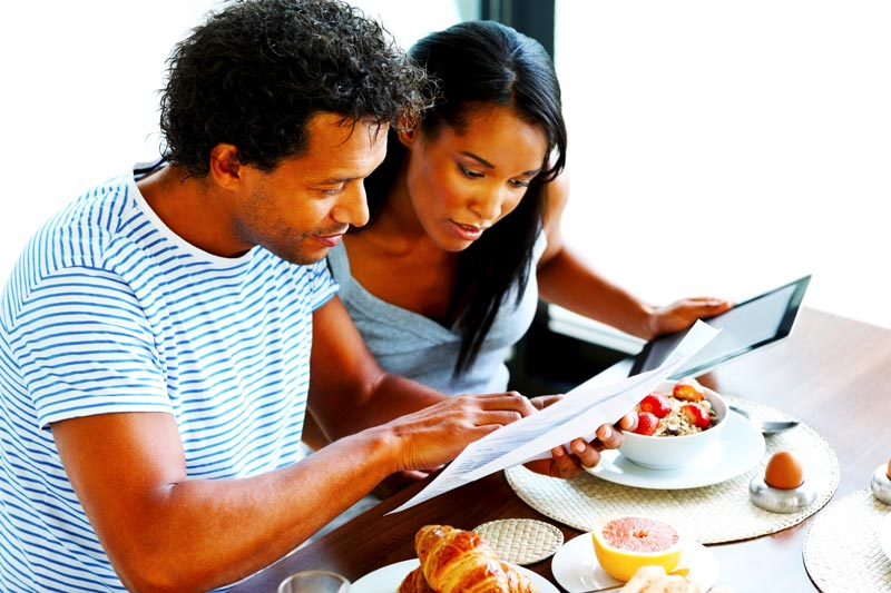 A couple wearing t-shirts paying their restaurant bill on a tablet